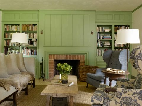 Large storage unit wall encases fireplace in a lustrous green paint, which is further enhanced with thick panel mould. Image Source: ELLEDECOR.